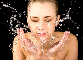 What Is The Best Way To Cleanse? — A Woman With Rosacea Cleansing Her Face, Splashing.
